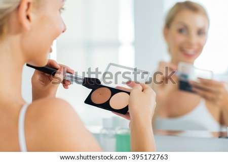 beauty, make up, cosmetics, morning and people concept - close up of happy young woman with makeup brush and contouring and highlighting palette looking to mirror at home bathroom - stock photo