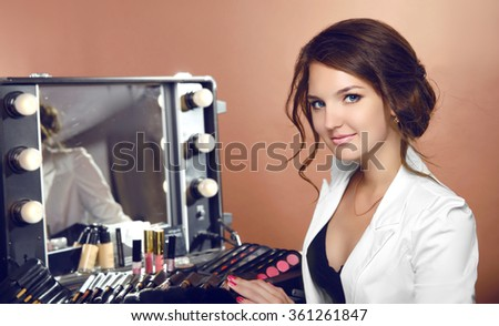 Beauty makeup artist woman with cosmetics by mirror in dressing room. Attractive female face Portrait. Professional stylist. - stock photo