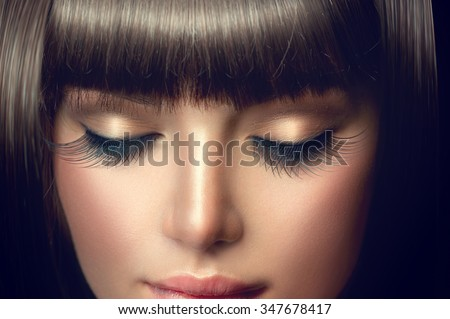 Beauty model girl face with perfect long eyelashes and fringe hairstyle. Brunette young woman face makeup closeup. Make up. Eyelash extensions - stock photo