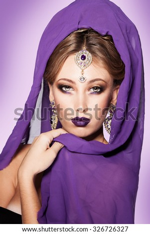 Beauty Model girl in a black dress and purple scarf. Oriental jewelry. Fashion makeup with purple tinge. Hairstyle.  - stock photo