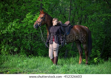 Beauty model girl in equestrian hunt uniform posing with horse - stock photo