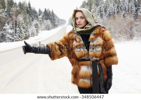 Beauty model girl in winter time. beautiful young Woman in fashionable Fur Coat,leather gloves and scarf. siberian snow around - stock photo