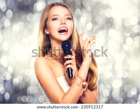 Beauty model girl singer with a microphone singing and dancing over holiday glowing background. Karaoke party singer. Disco party. Celebration - stock photo