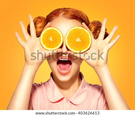 Beauty Model Girl takes Juicy Oranges. Beautiful Joyful teen girl with freckles, funny red hairstyle and yellow makeup. Professional make up. Holding Orange Slices and laughing, emotions - stock photo