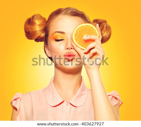 Beauty Model Girl takes Juicy Oranges. Beautiful Joyful teen girl with freckles, funny red hairstyle and yellow makeup. Professional make up. Orange Slice  - stock photo