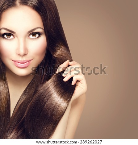 Beauty Model girl with Healthy Brown Hair. Beautiful brunette woman touching her long smooth shiny straight hair. Hairstyle. Hair cosmetics, haircare. Hair care, extensions. Brown background - stock photo