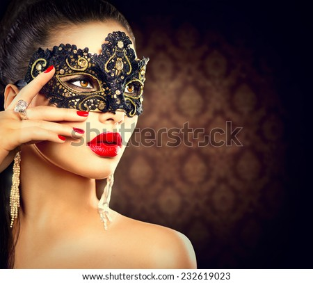 Beauty model woman wearing venetian masquerade carnival mask at party, over holiday dark background. Christmas and New Year celebration. Sexy girl with holiday makeup and manicure. Red lips and nails - stock photo