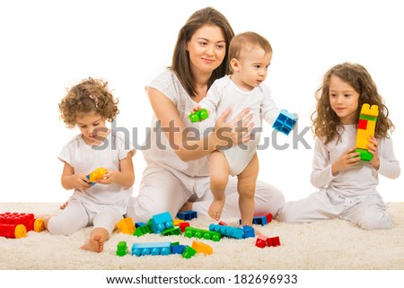Beauty mom playing with her three kids home and sitting together on fur carpet - stock photo