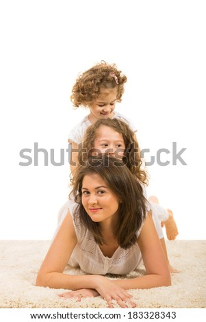 Beauty mother laying on fur carpet and her daughter sitting on her back - stock photo