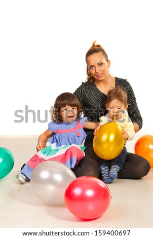 Beauty mother with her kids and balloons sitting down on floor - stock photo