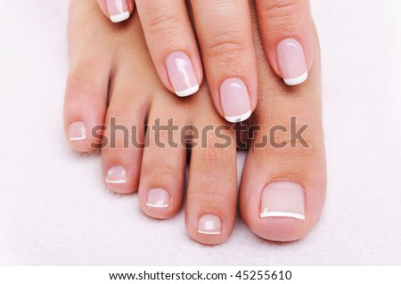 Beauty nails concept of a female hand and feet with beautiful french manicure and pedicure - stock photo