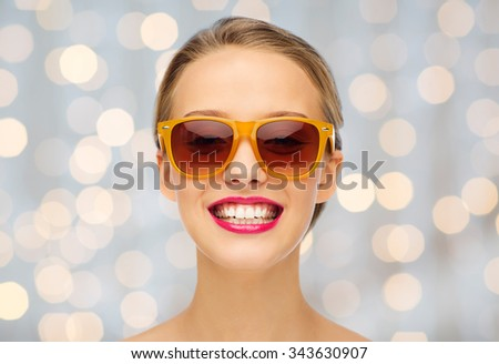 beauty, people, accessory and fashion concept - smiling young woman in sunglasses with pink lipstick on lips over holidays lights background - stock photo