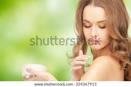 beauty, people and health concept - beautiful smiling woman cleaning face skin with cotton pad over blue background - stock photo