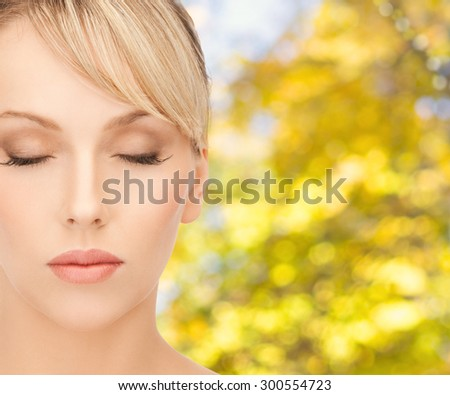 beauty, people and health concept - beautiful young woman face in make-up over yellow autumn background - stock photo