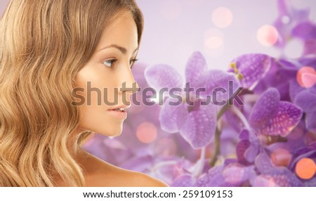 beauty, people and health concept - beautiful young woman face over purple orchid flowers background - stock photo