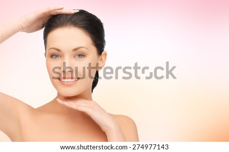 beauty, people and health concept - beautiful young woman touching her face and chin over pink background - stock photo