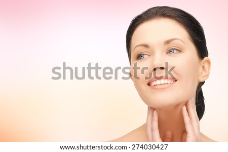 beauty, people and health concept - beautiful young woman touching her face and neck over pink background - stock photo
