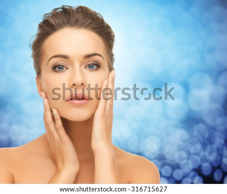 beauty, people and health concept - beautiful young woman touching her face over blue lights background - stock photo