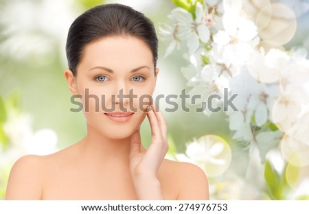 beauty, people and health concept - beautiful young woman touching her face over green blooming garden background - stock photo