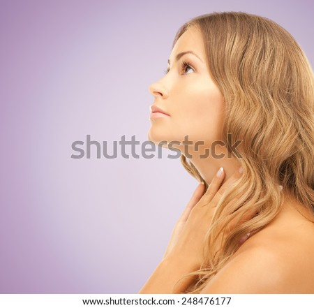 beauty, people and health concept - beautiful young woman touching her neck and looking up over violet background - stock photo