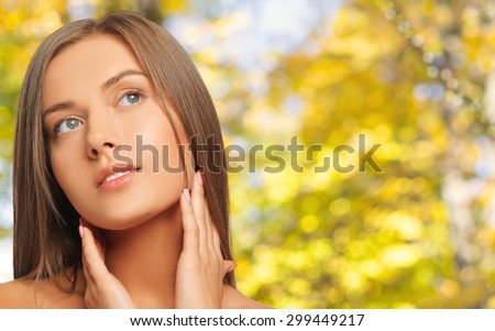 beauty, people and health concept - beautiful young woman touching her neck over yellow autumn background - stock photo