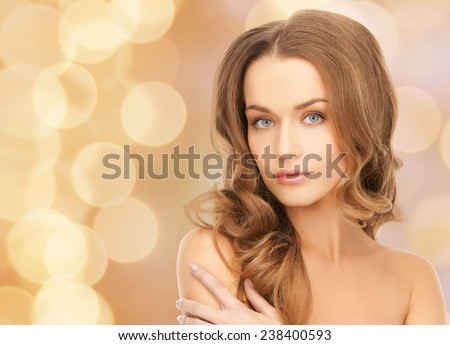 beauty, people and health concept - beautiful young woman with bare shoulders over beige lights background - stock photo