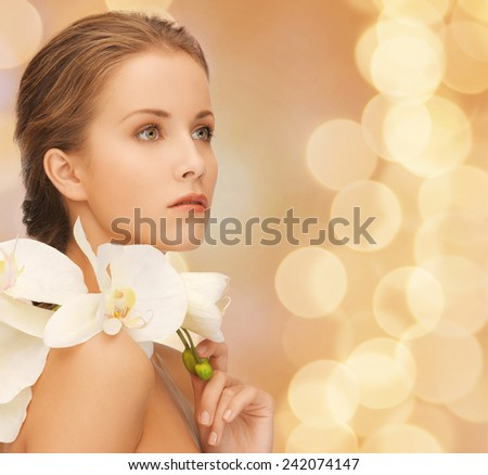 beauty, people and health concept - beautiful young woman with orchid flowers and bare shoulders over beige lights background - stock photo