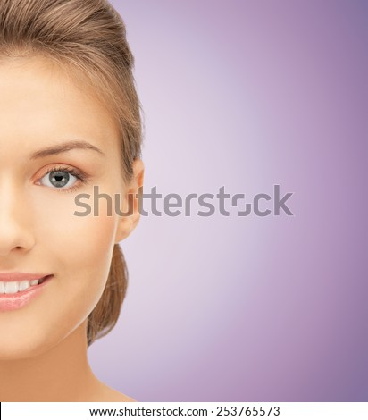 beauty, people and health concept - close up of beautiful young woman half face over violet background - stock photo