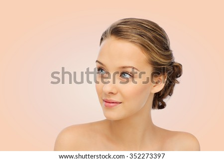 beauty, people and health concept - smiling young woman face and shoulders over beige background - stock photo
