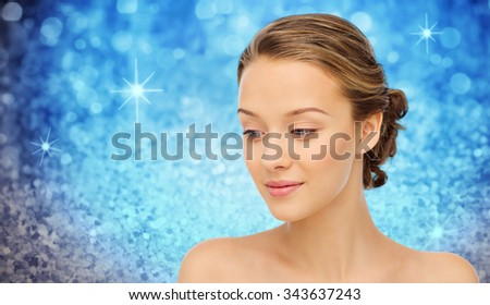 beauty, people and health concept - smiling young woman face and shoulders over blue holidays lights or glitter background - stock photo