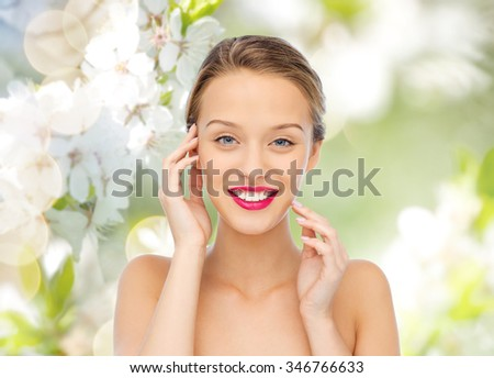 beauty, people and health concept - smiling young woman face with pink lipstick on lips and shoulders over green natural background with cherry blossoms - stock photo