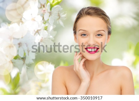 beauty, people and health concept - smiling young woman face with pink lipstick on lips and shoulders over green natural cherry blossom background - stock photo