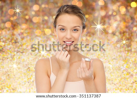 beauty, people and lip care concept - smiling young woman applying lip balm to her lips over golden glitter background - stock photo