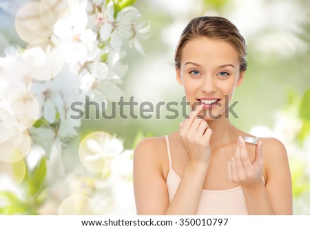 beauty, people and lip care concept - smiling young woman applying lip balm to her lips over green natural cherry blossom background - stock photo