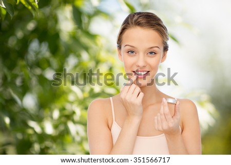 beauty, people and lip care concept - smiling young woman applying lip balm to her lips over green natural background - stock photo