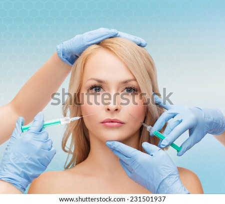 beauty, people and plastic surgery concept - woman face and beautician hands with syringes - stock photo