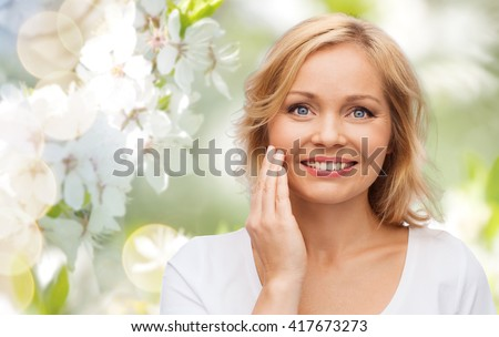 beauty, people and skincare concept - smiling woman in white shirt touching face over natural spring cherry blossom background - stock photo
