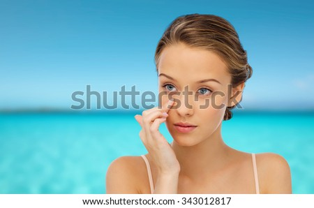beauty, people, cosmetics, skincare and health concept - young woman applying cream to her face over blue sea and sky background - stock photo