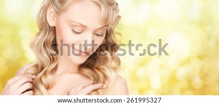 beauty, people, hair care and health concept - beautiful young woman face with long wavy hair over yellow lights background - stock photo