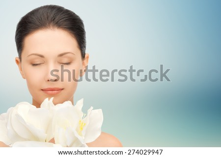 beauty, people, holidays and health concept - beautiful young woman smelling flowers with closed eyes over blue background - stock photo