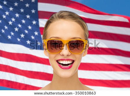 beauty, people, nationality and patriotism concept - smiling young woman in sunglasses with pink lipstick on lips over american flag background - stock photo
