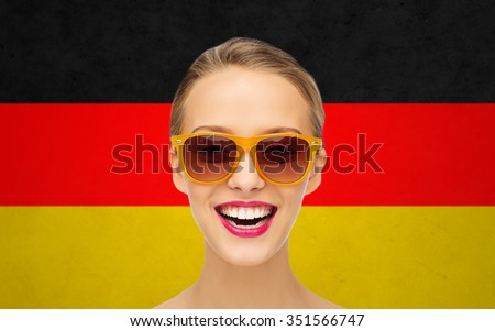 beauty, people, nationality and patriotism concept - smiling young woman in sunglasses with pink lipstick on lips over german flag background - stock photo