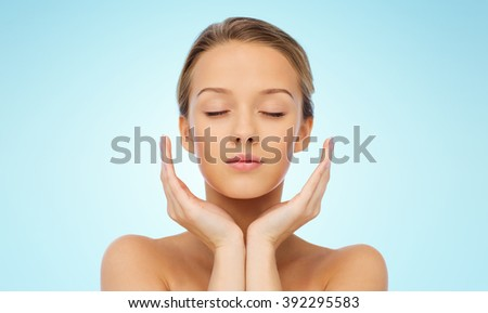 beauty, people, skincare and health concept - young woman face and hands over blue background - stock photo