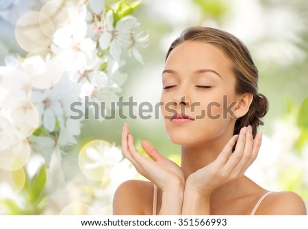 beauty, people, skincare, summer and health concept - young woman face and hands over green natural background with cherry blossom - stock photo