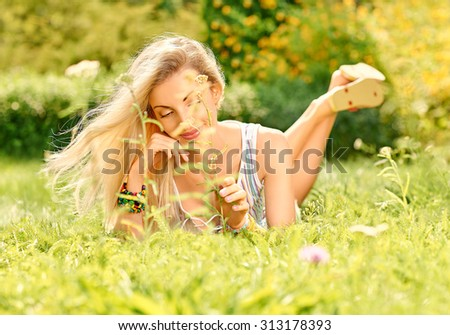 Beauty playful woman relax in summer green garden lying on grass, bokeh. Attractive happy blonde girl enjoying nature, harmony, outdoor on meadow, lifestyle. Sunny day, forest, flowers, copyspace - stock photo