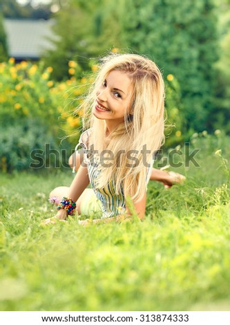 Beauty playful woman relax in summer green garden smiling on grass, bokeh. Attractive happy blonde girl enjoying nature, harmony, outdoor on meadow, lifestyle. Sunny day, forest, flowers, copyspace - stock photo