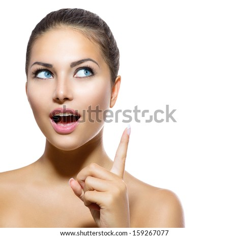 Beauty Portrait. Beautiful Spa Girl showing Finger Up. Surprised Woman Looking Up. Isolated on white background. Fresh Clean Skin. Skin Care Concept - stock photo