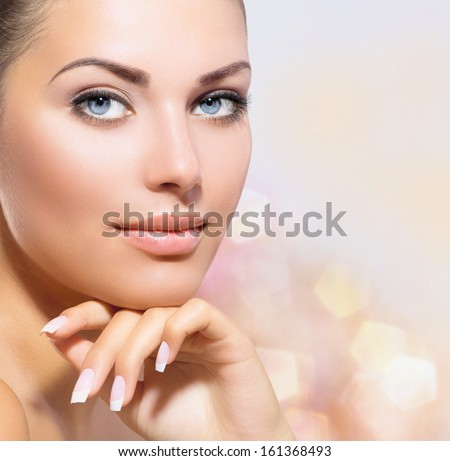 Beauty Portrait. Beautiful Spa Woman Touching her Face. Perfect Fresh Skin closeup. Over Pink Blurred Background. Pure Beauty Model. Youth and Skin Care Concept  - stock photo