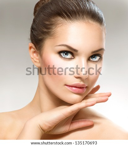 Beauty Portrait. Beautiful Spa Woman Touching her Face. Perfect Fresh Skin. Pure Beauty Model. Youth and Skin Care Concept - stock photo