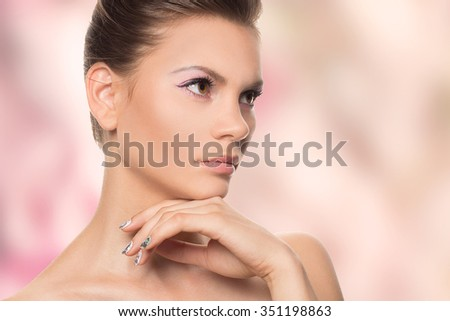 Beauty Portrait. Beautiful Spa Woman Touching her Face. Perfect Fresh Skin. Youth and Skin Care Concept. Studio shot over color background. - stock photo